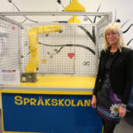 Siv Stenlund in front of the Fanuc robot.
